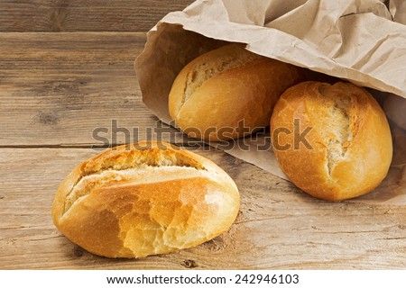 bread rolls in a paper bag on a rustic wooden table, fresh from the bakery for breakfast - stock photo