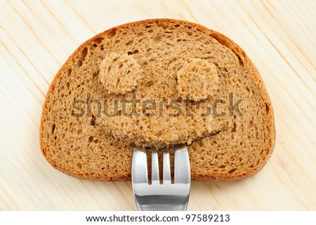 Bread slice as smiling face with with a fork in your mouth - stock photo