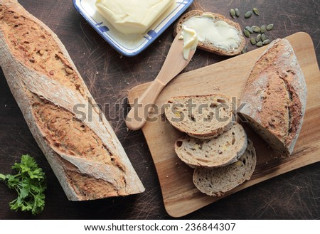 Bread slices with butter on wooden board - stock photo