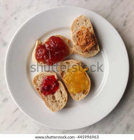 Bread slices with orange marmalade, strawberry jam, redberry jam and peanut butter - stock photo