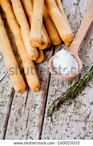 bread sticks grissini with rosemary and salt closeup on rustic wooden background - stock photo