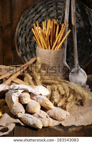 Bread sticks on sackcloth on wooden background - stock photo