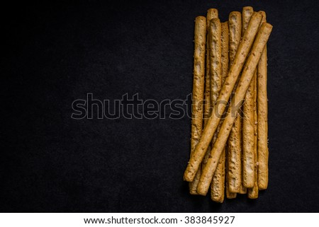 Bread sticks with salt and herbs on dark board, from overhead. - stock photo