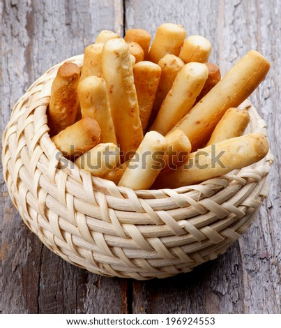 Bread Sticks with Sesame Seeds in Wicker Bowl isolated on Rustic Wooden background - stock photo