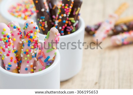 Bread sticks with strawberry chocolate and colorful sprinkles for children, Snack for kids - stock photo