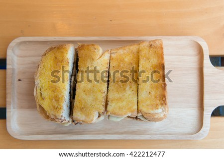 Bread toast with butter ,banana slice and chocolate topping on wooden plate.  - stock photo