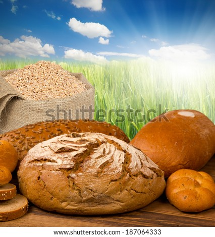 Bread with buns on wooden desk with green field and sky - stock photo