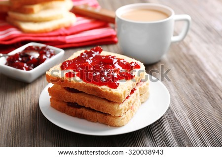 Bread with butter and homemade jam on wooden table, closeup - stock photo