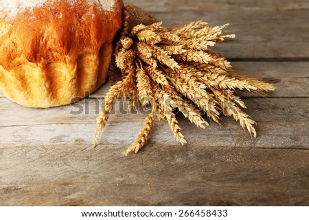 Bread with ears on wooden background - stock photo