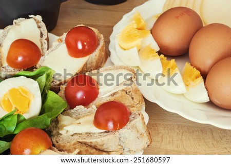 Bread with eggs, cherry tomatoes and green lettuce for breakfast. - stock photo