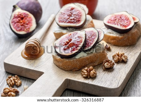 bread with figs, ricotta, honey and walnuts on a cutting board - stock photo