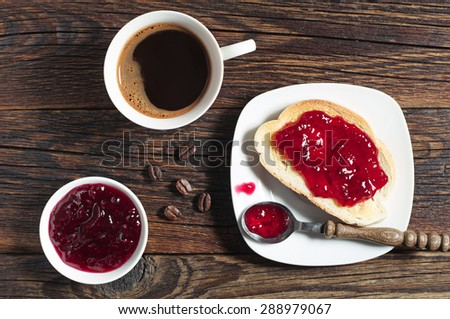 Bread with jam and coffee cup for breakfast on dark wooden table, top view - stock photo
