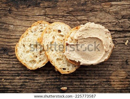 bread with liver pate on old wooden table - stock photo