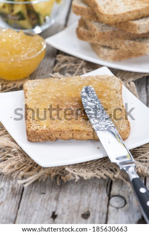 Bread with Pineapple Jam on a small plate (wooden background) - stock photo