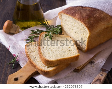 Bread with rosemary on a wooden table - stock photo