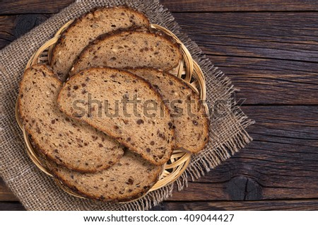 Bread with seeds, dried fruit and nuts slices in plate on old wooden table. Top view - stock photo
