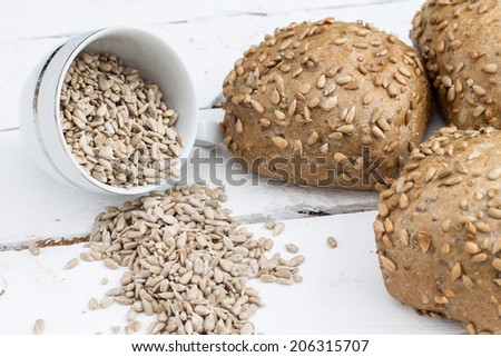Bread with sunflower seeds. Composition on a white wooden board. - stock photo