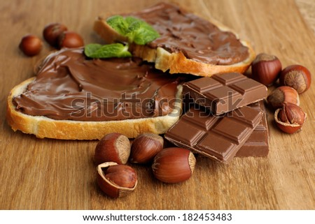 Bread with sweet chocolate hazelnut spread on wooden background - stock photo