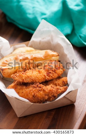 breaded chicken fingers and fries in a take out container - stock photo