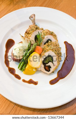 Breaded chicken slices stuffed with sweet peppers and served with asparagus and vegetables. Drizzled with balsamic vinegar. - stock photo