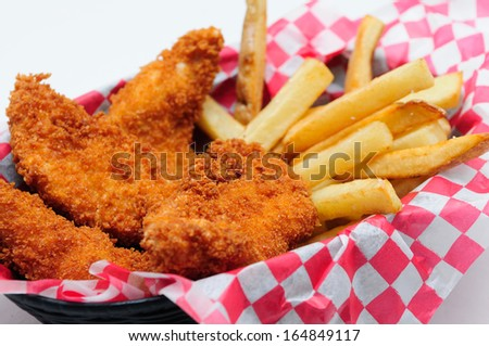 breaded chicken strips with french fries and dipping sauce in a diner basket - stock photo