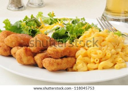 Breaded chicken strips with macaroni and cheese and salad - stock photo