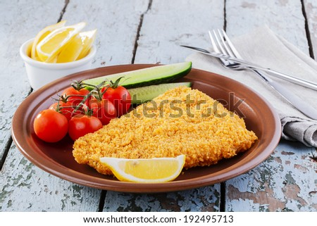 Breaded fish fillet with vegetables - stock photo