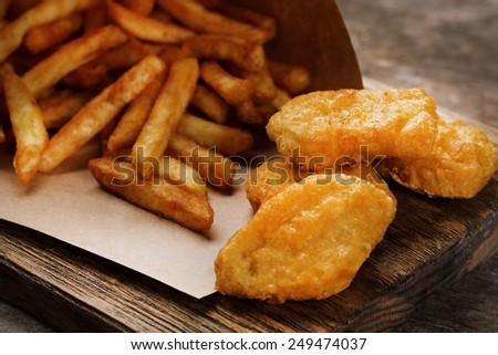 Breaded fried chicken nuggets and potatoes in paper bag on cutting board and rustic wooden background - stock photo
