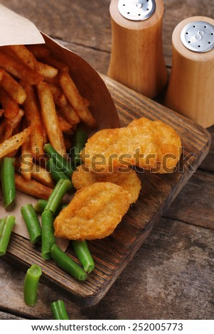 Breaded fried chicken nuggets and potatoes in paper bag with asparagus on cutting board and rustic wooden background - stock photo