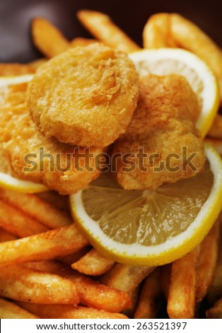Breaded fried chicken nuggets and potatoes with sliced lemon, macro view - stock photo