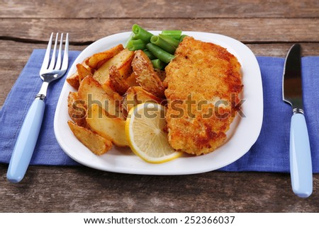 Breaded fried fish fillet and potatoes with asparagus and lemon on plate and wooden planks background - stock photo