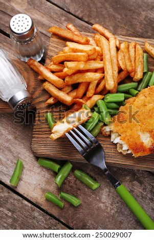 Breaded fried fish fillet and potatoes with asparagus on cutting board and wooden planks background - stock photo