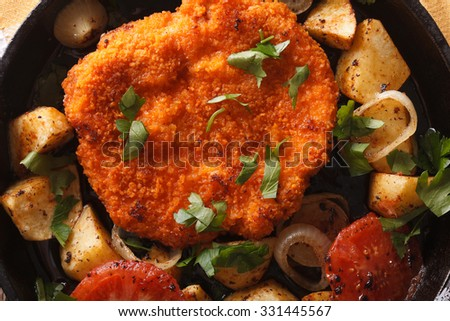 breaded German Weiner schnitzel, fried potatoes in a pan close-up. horizontal view from above - stock photo