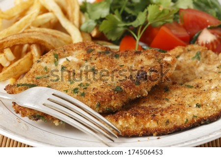 breaded homemade chicken schnitzels or escalopes with french fries and a tomato and green salad - stock photo