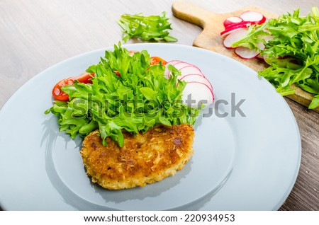 Breaded pork chops in Parmesan cheese, lettuce and radish and cherry tomatoes - stock photo