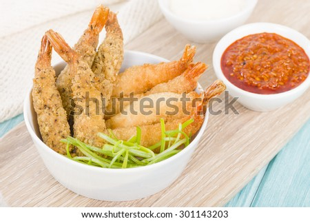 Breaded Prawns - King prawns coated in plain and spicy breadcrumbs and deep-fried. - stock photo