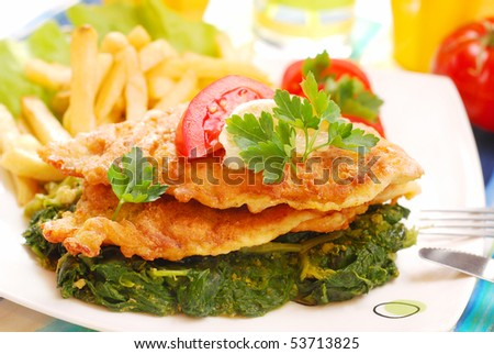 breaded sole fish  on spinach with french fries for dinner - stock photo