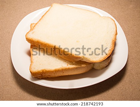 breads on dish  against wooden table surface - stock photo