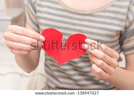 Break red heart in beautiful female hands (fingers) in bedroom. Conflict in couple, problems, divorce and pain concept. - stock photo