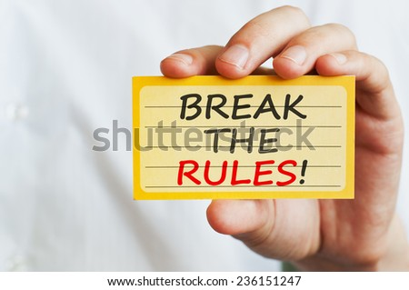 Break the Rules! Man holding a card with motivational message text written on it - stock photo