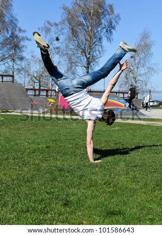 Breakdancer doing a flip on the grass. - stock photo