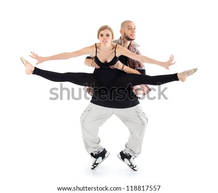 Breakdancer holds ballerina in black and stands on tiptoes isolated on white background. Woman stretched legs in twine and spread her arms to sides. - stock photo