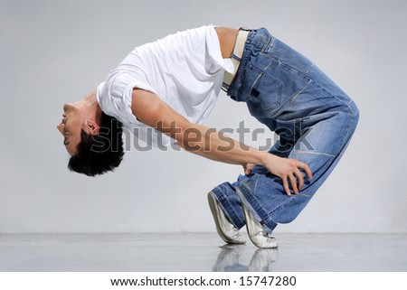 breakdancer posing on a grey background - stock photo