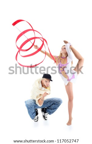 Breakdancer squats and points his finger at camera and gymnast girl with red ribbon stands on one leg, other leg placed on head isolated on white background. - stock photo