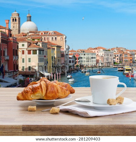 Breakfast at Venice - cup of coffee with croissant by Grand Canal, Italy - stock photo
