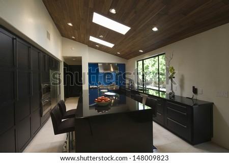 Breakfast bar in modern kitchen with skylights - stock photo