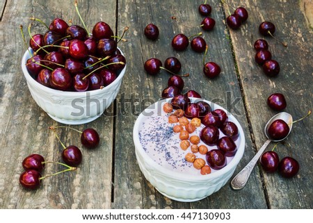 Breakfast bowl with yogurt, granola or muesli or oat flakes, fresh cherries and nuts. Ripe berries and retro spoon on old vintage wooden background - stock photo