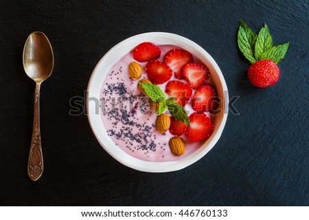 Breakfast bowl with yogurt, granola or muesli or oat flakes, fresh strawberry and mint. Black stone background. Top view. - stock photo