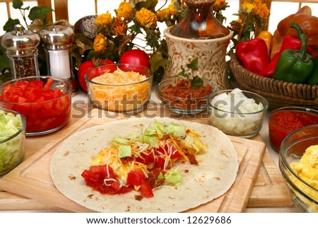 Breakfast burrito in kitchen or restaurant.  Eggs, cheese, tomato, lettuce, onion, chipotle, bacon. - stock photo