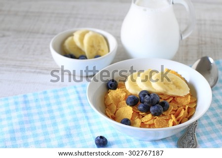 Breakfast cereal with blueberries, bananas and milk on a rustic wood table - stock photo